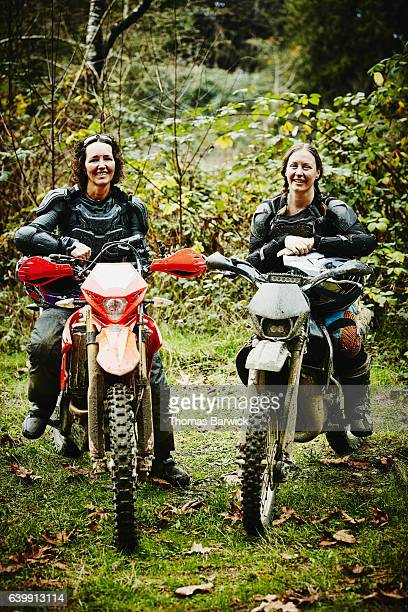 Smiling female motorcyclists sitting on dirt bikes after ride