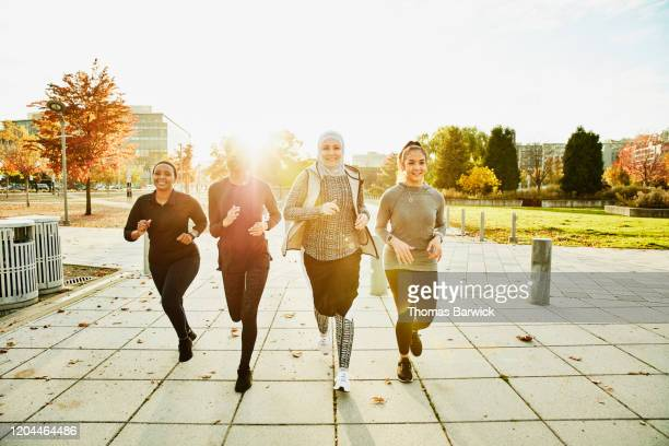 smiling female muslim athletes on afternoon run - athlete stock pictures, royalty-free photos & images