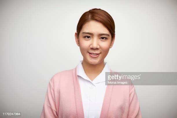 smiling female nurse against white background - oost azië stockfoto's en -beelden