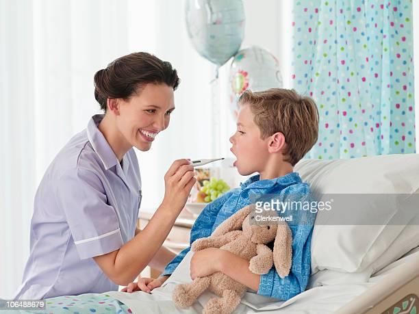 Souriant peu Infirmière vérification garçon (10 et 11) température i