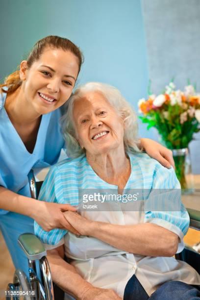 mãos fêmeas de sorriso da terra arrendada da enfermeira da mulher sênior - izusek - fotografias e filmes do acervo