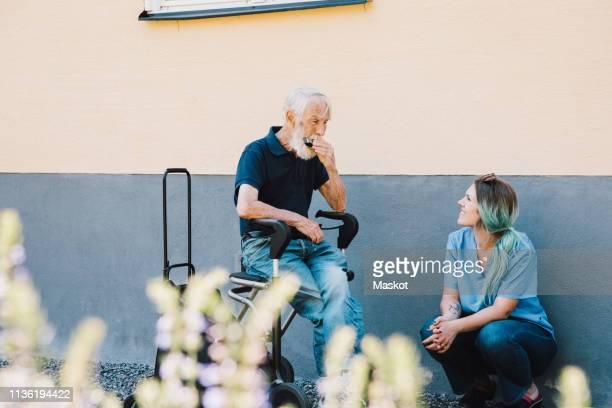 smiling female nurse looking at senior man playing harmonica against wall at back yard - maatschappelijk werker stockfoto's en -beelden