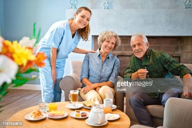 enfermeira fêmea de sorriso que está por pares sênior - izusek - fotografias e filmes do acervo