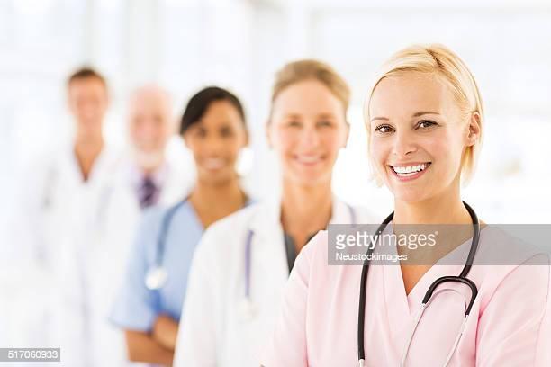 Infirmière souriante avec une équipe médicale
