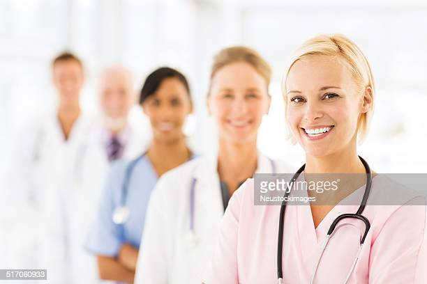 Smiling Female Nurse With Medical Team