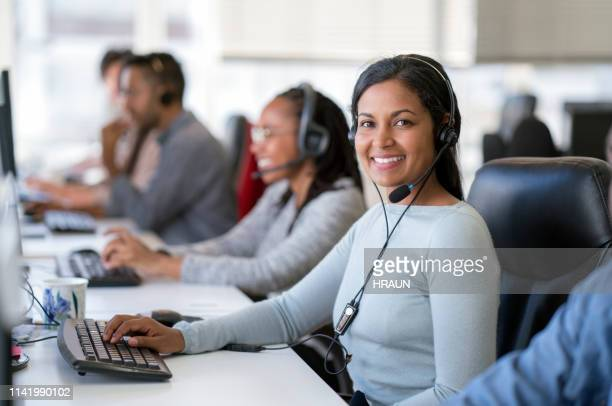 smiling female operator working in call center - call center stock pictures, royalty-free photos & images
