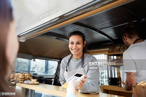 Smiling female owner accepting credit card payment from customer at concession stand