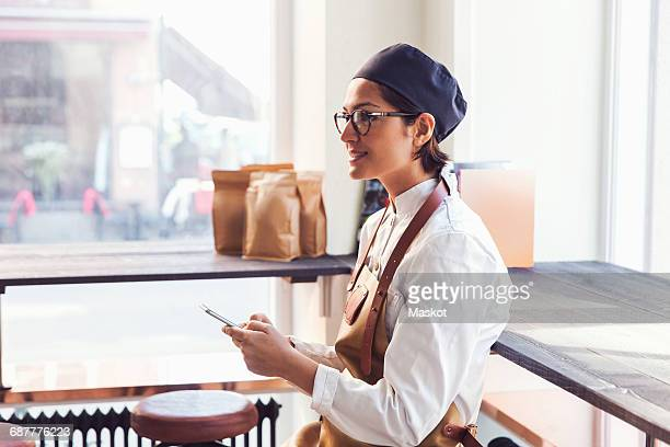 Smiling female owner holding smart phone while standing by window in grocery store
