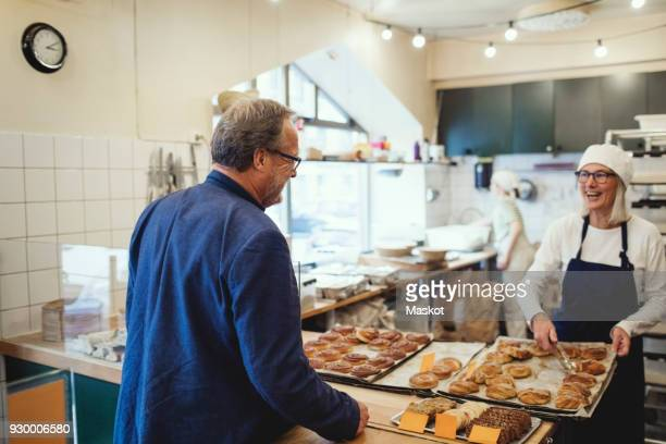 Smiling female owner showing fresh baked food to customer at bakery