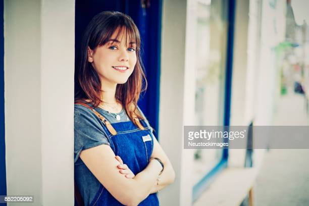 Smiling female owner standing arms crossed outside deli