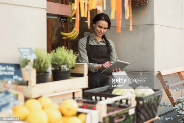Smiling female owner using digital tablet while sitting at store entrance