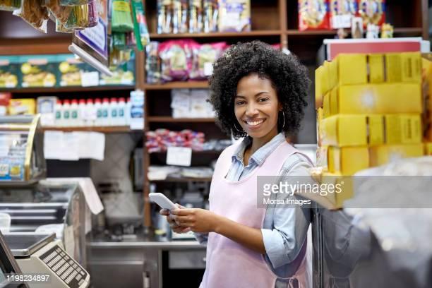 proprietário fêmea de sorriso com telefone esperto na loja - empreendedor - fotografias e filmes do acervo