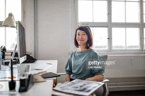smiling female professional at her desk - focus on background stock pictures, royalty-free photos & images