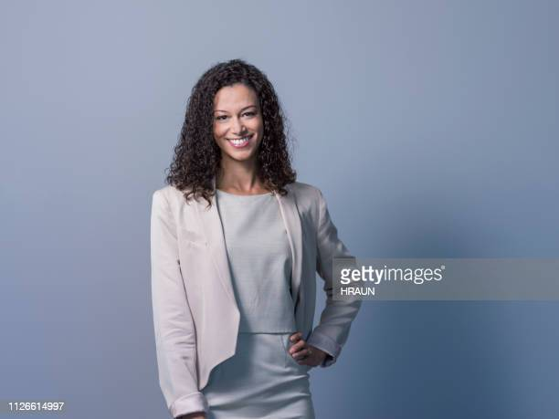 smiling female professional with hand on hip - mid length hair stock pictures, royalty-free photos & images
