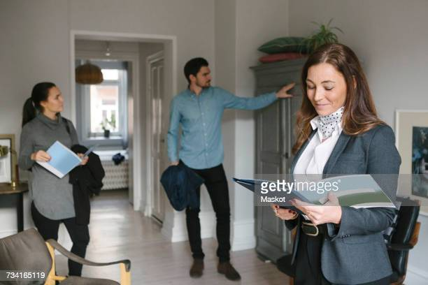 Smiling female real estate agent reading brochure while couple looking at cabinet at home