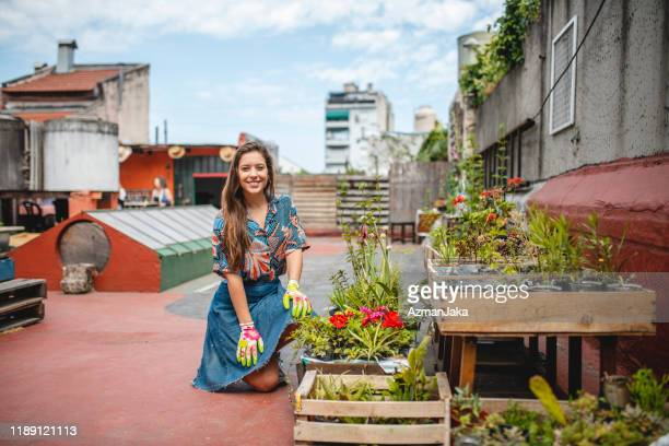 smiling female roof gardener kneeling next to planter boxes - urban garden stock pictures, royalty-free photos & images