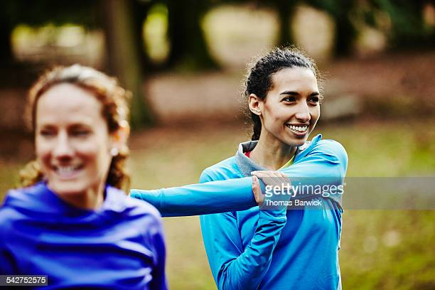 smiling female runner stretching with friends - warming up stock pictures, royalty-free photos & images