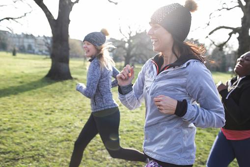 Smiling female runners running in sunny park - gettyimageskorea
