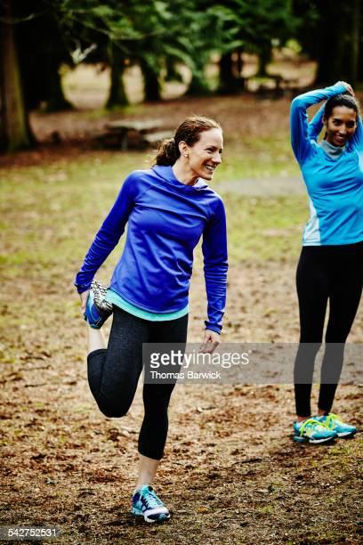 Smiling female runners stretching before run