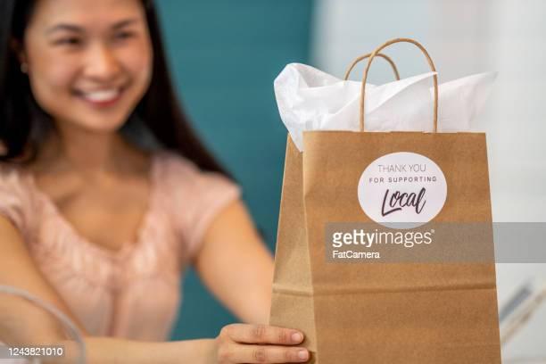 笑顔の女性店主が「地元を支えてくれてありがとう」ステッカーでクラフトバッグを掲げる - ギフトショップ ストックフォトと画像