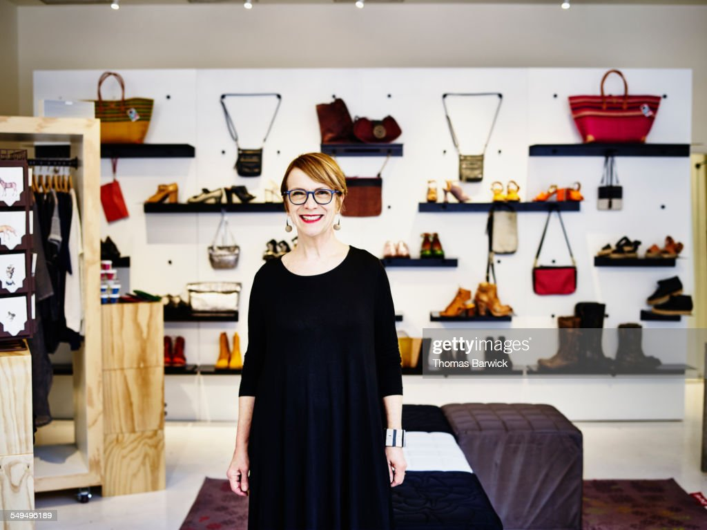 Smiling female shop owner standing in boutique : Stock Photo