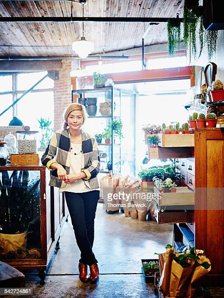 Smiling female shop owner standing in plant store