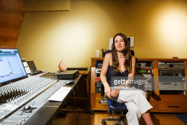 smiling female singer sitting in recording studio - recording studio stock pictures, royalty-free photos & images