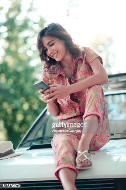 smiling female sitting on retro style car and texting on smartphone - very young webcam girls stock photos and pictures