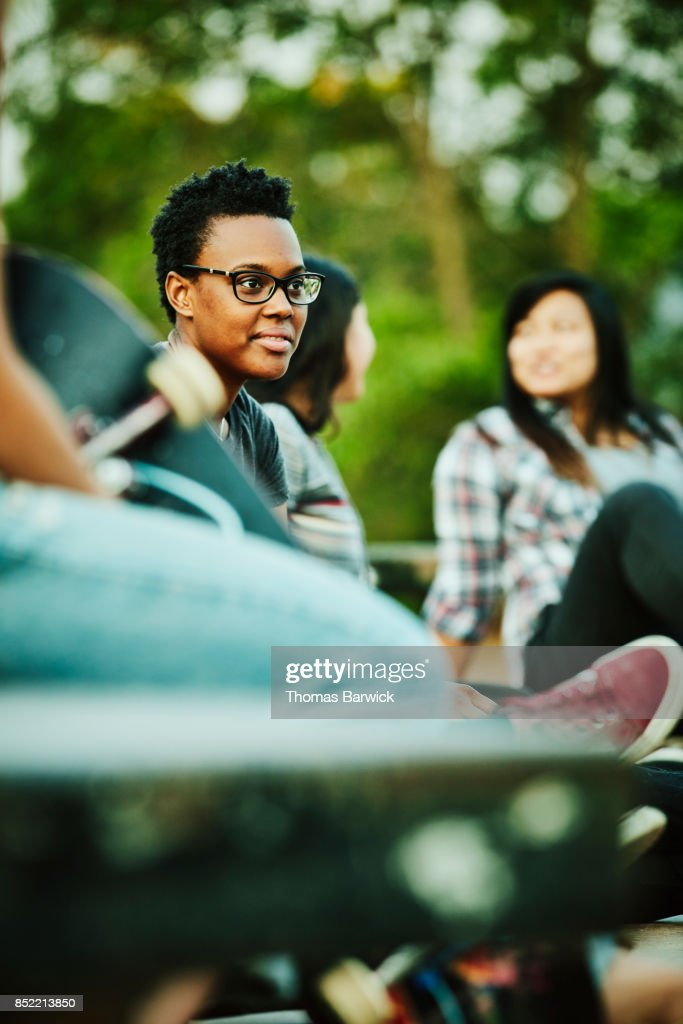 Smiling female skater hanging out with friends at skate park : Stock Photo