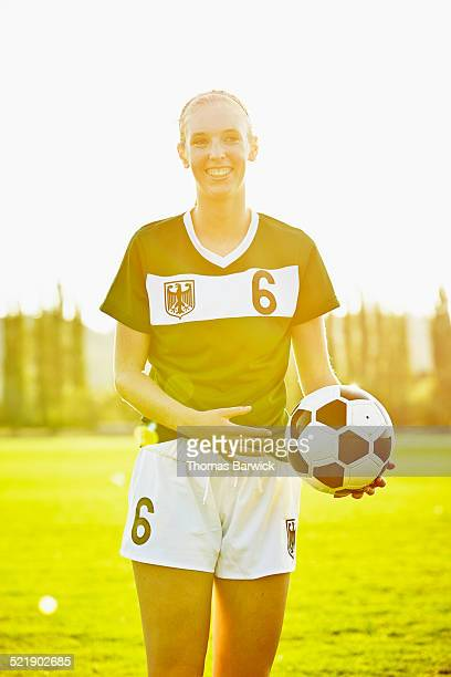Smiling female soccer player standing on field