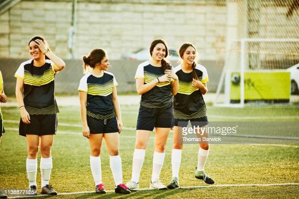 smiling female soccer team warming up on field before game - warming up stock pictures, royalty-free photos & images