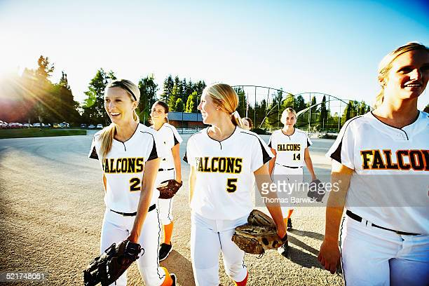 Smiling female softball team walking off of field
