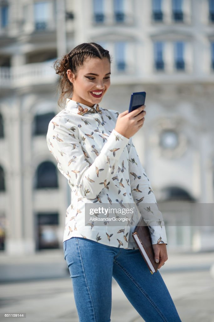 Smiling Female Student Holding Book and Texting on Smartphone : Stock Photo