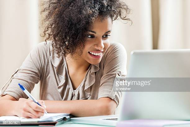 Smiling female student studying at home.