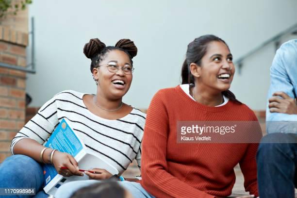 smiling female students looking at male friend - middelste deel stockfoto's en -beelden