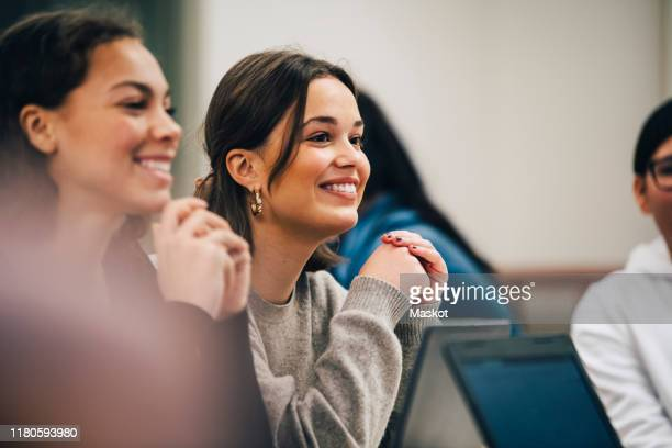 smiling female students looking away while sitting in classroom - person in education stock pictures, royalty-free photos & images
