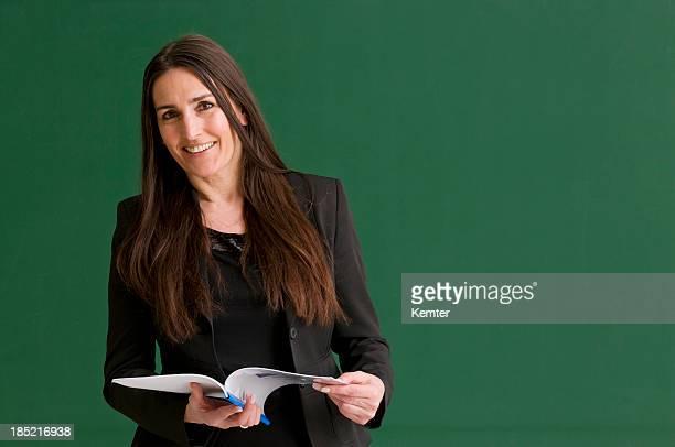 Smiling female teacher against a green chalkboard.