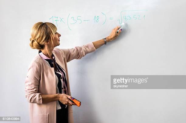 Smiling female teacher writing mathematics formula on whiteboard.