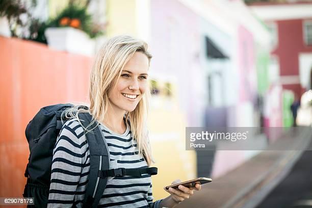 smiling female tourist holding smart phone - rucksack stock-fotos und bilder