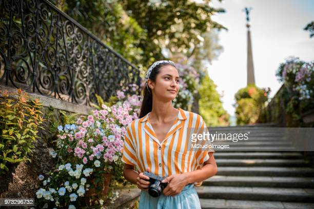 smiling female tourist with camera. - human settlement stock pictures, royalty-free photos & images