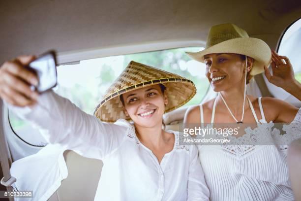 Smiling Female Tourists how Take a Selfie inside of Car