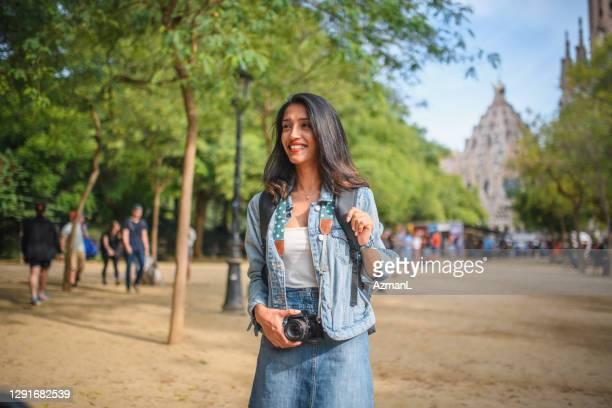 viaggiatrice sorridente con macchina fotografica nella soleggiata barcellona - europa meridionale foto e immagini stock