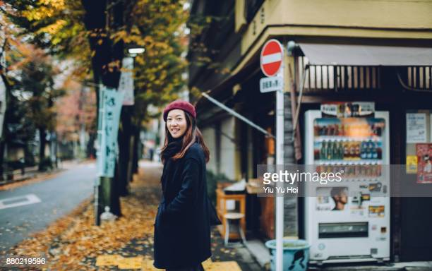 smiling female traveller walking under fallen maple leaves in street in tokyo - hands in pockets stock photos and pictures