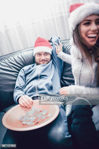 Smiling Female Trying to Wake up her Drunk Boyfriend on New Year's Eve