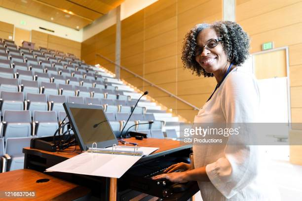 smiling female university professor pauses work to pose for photo - post secondary education stock pictures, royalty-free photos & images