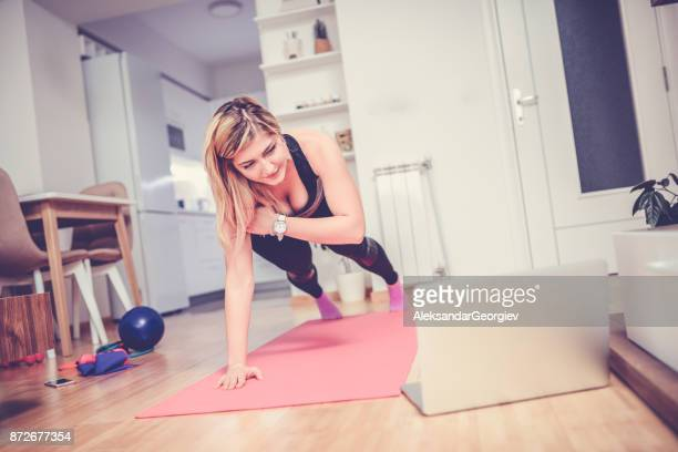 smiling female watching exercises on laptop and training at home - plank exercise stock pictures, royalty-free photos & images