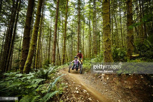 smiling female wheelchair athlete descending down trail on adaptive mountain bike with friend - forward athlete stock pictures, royalty-free photos & images
