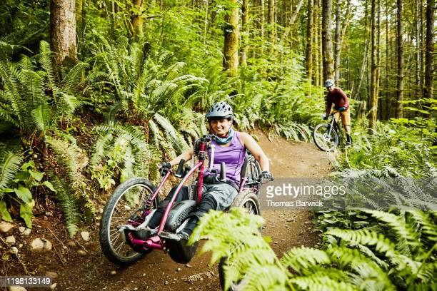 smiling female wheelchair athlete riding adaptive mountain bike on trail with friend - forward athlete stock pictures, royalty-free photos & images