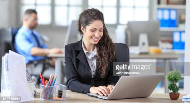 スマート フォンで話している女性のホワイト カラー労働者を笑顔
