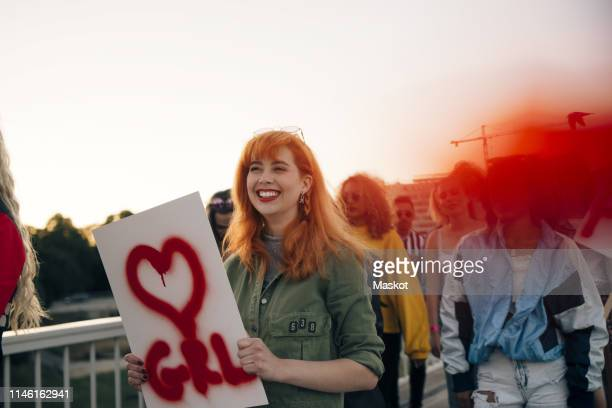 smiling female with friends marching for women's rights in city against sky - marching stock pictures, royalty-free photos & images